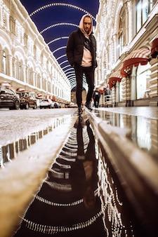 Mężczyzna w kapturze w nocy na deszczowej ulicy.