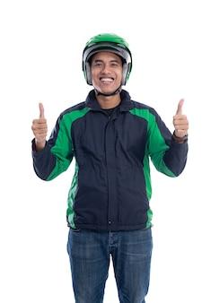 Mężczyzna w kasku i kurtce lub mundurze komercyjnego taksówkarza online pokazuje kciuk w górę