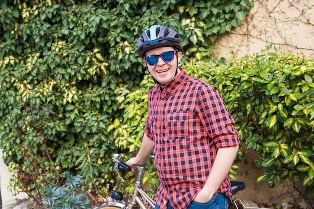 Mężczyzna w kasku i okularach zostaje przy rowerze