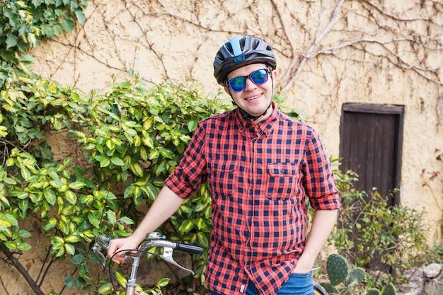 Mężczyzna w kasku i okularach zostaje w ogrodzie na ścianie roweru