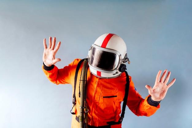 Mężczyzna w kasku i pomarańczowym garniturze astronauty