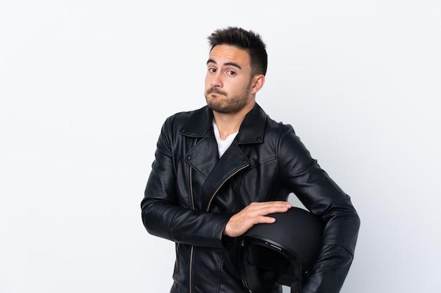 Mężczyzna w kasku motocykla gestem wątpliwości, podnosząc ramiona
