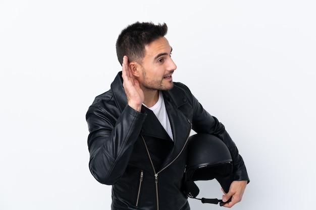 Mężczyzna w kasku motocykla, słuchając czegoś, kładąc rękę na uchu