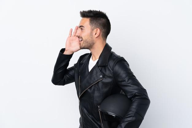 Mężczyzna w kasku motocyklowym krzyczy z szeroko otwartymi ustami do boku