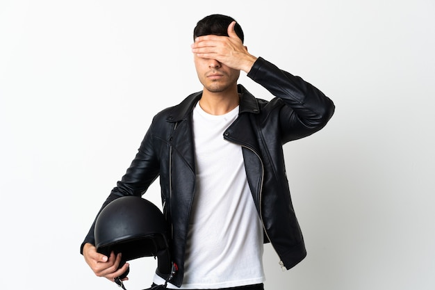 Mężczyzna w kasku motocyklowym na białym tle na białe zasłaniające oczy rękami.