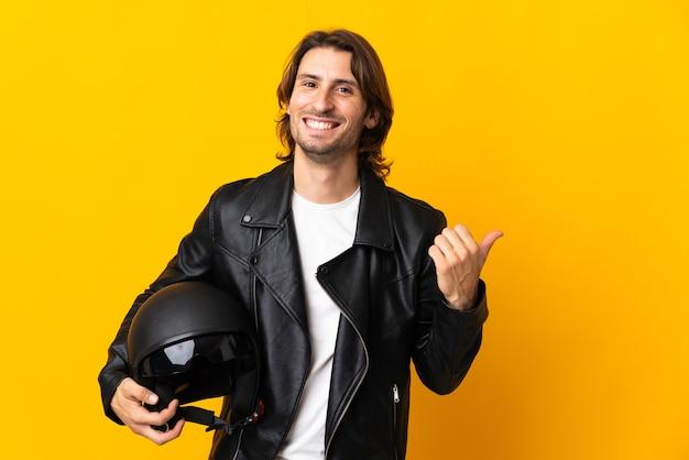 Mężczyzna w kasku motocyklowym na żółtym tle, wskazując na bok, aby przedstawić produkt