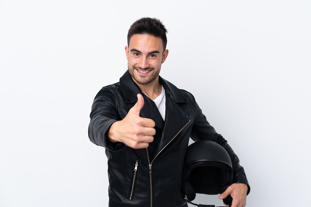 Mężczyzna w kasku motocyklowym z kciukami do góry, ponieważ stało się coś dobrego