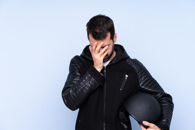 Mężczyzna w kasku motocyklowym z wyrazem zmęczenia i choroby