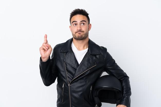 Mężczyzna w kasku motocyklowym ze skrzyżowanymi palcami i życzący najlepszego