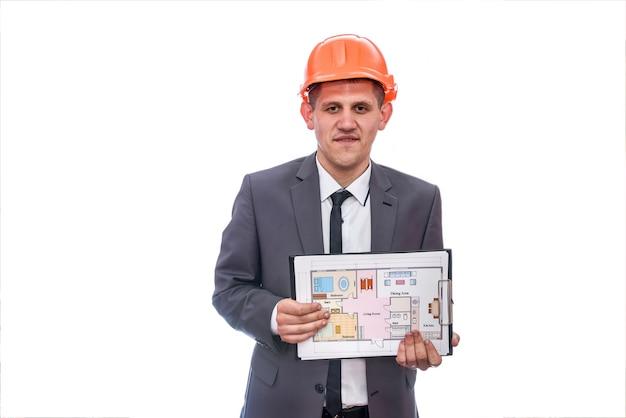 Mężczyzna w kasku przedstawiający plan domu na białym tle