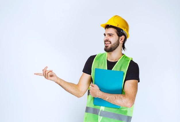 Mężczyzna w kasku trzymający niebieską teczkę i wskazujący kogoś po lewej stronie.