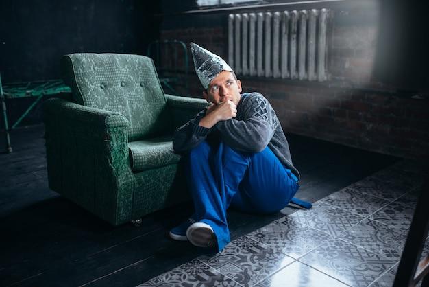Mężczyzna w kasku z folii aluminiowej ogląda telewizję, ochrona umysłu