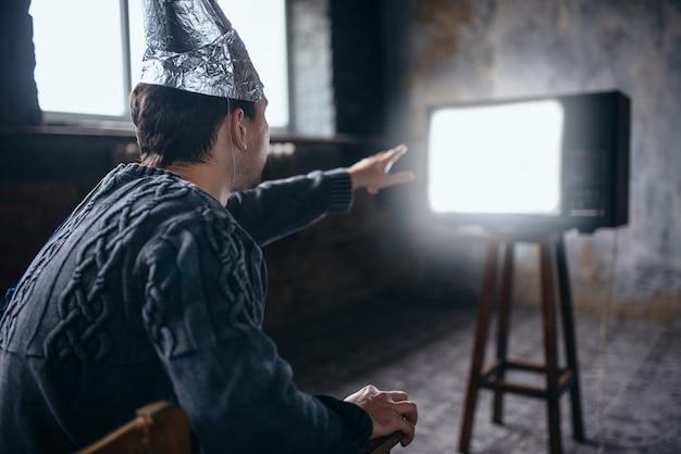 Mężczyzna w kasku z folii aluminiowej sięga do telewizora