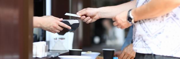 Mężczyzna w kawie płaci kartą kredytową w terminalu na tacy z jedzeniem. koncepcja bezpiecznych płatności kartami bankowymi w miejscach publicznych
