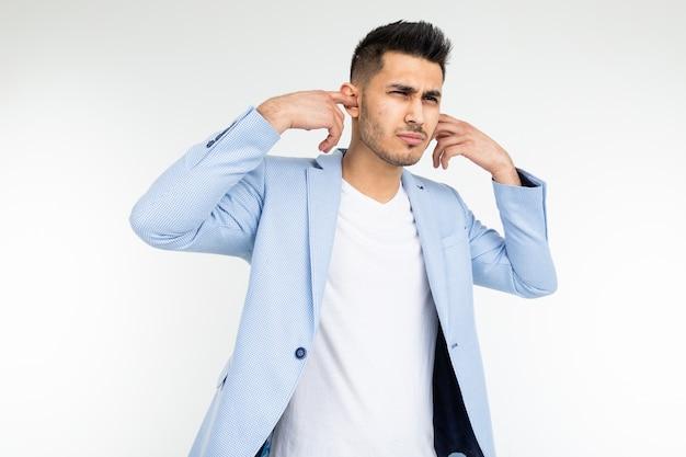Mężczyzna w klasycznej niebieskiej marynarce zakrywa uszy palcami