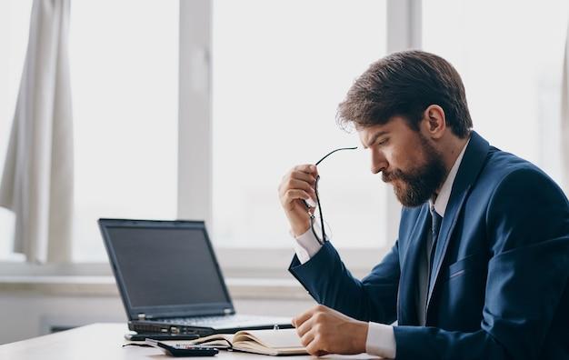 Mężczyzna w klasycznym garniturze siedzi przy stole, a przy otwartym oknie biura laptopa wygląda zdziwiony. wysokiej jakości zdjęcie