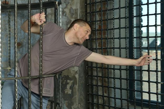 Mężczyzna w klatce z rękami na stalowej siatce