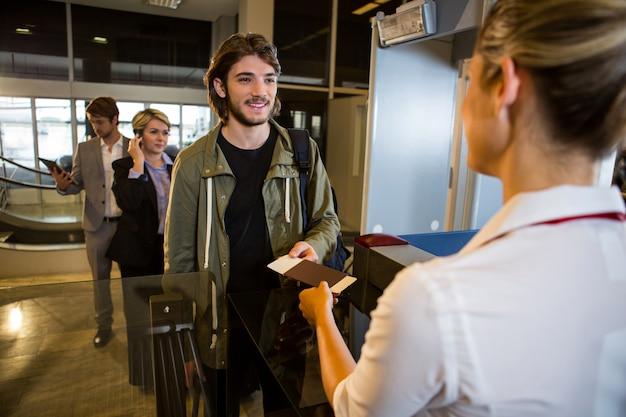 Mężczyzna w kolejce odbiera paszport i kartę pokładową