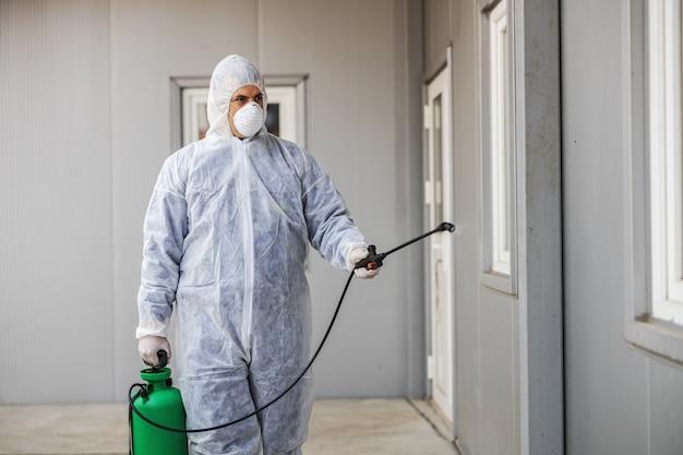 Mężczyzna w kombinezonie antywirusowym i masce dezynfekującej budynki koronawirusa opryskiwaczem. epidemia.