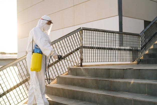 Mężczyzna w kombinezonie antywirusowym i masce dezynfekującej budynki koronawirusa opryskiwaczem. zapobieganie infekcjom i kontrola epidemii. światowa pandemia.