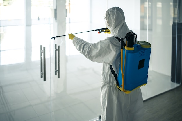 Mężczyzna w kombinezonie do dezynfekcji spryskuje klamki szklanych drzwi w pustym centrum handlowym środkiem dezynfekującym, aby zapobiec rozprzestrzenianiu się covid-19. świadomość zdrowotna, czystość, koncepcja obrony.