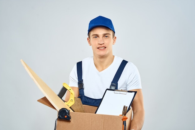 Mężczyzna w kombinezonie i czapce niosący pudełko