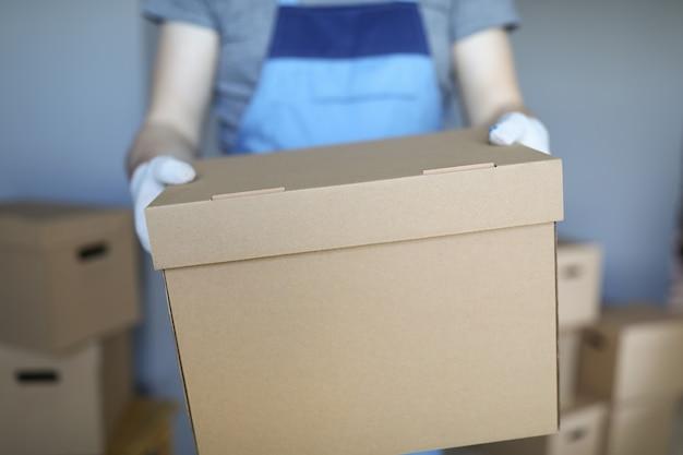 Mężczyzna w kombinezonie i rękawiczkach trzyma w dłoni duży karton