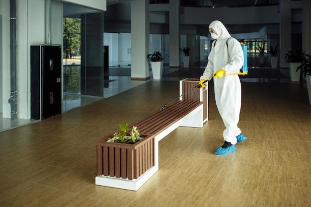 Mężczyzna w kombinezonie ochronnym dezynfekuje ławkę w pustym centrum handlowym sprayem dezynfekującym. oczyszczanie miejsca publicznego, aby zapobiec rozprzestrzenianiu się covid.