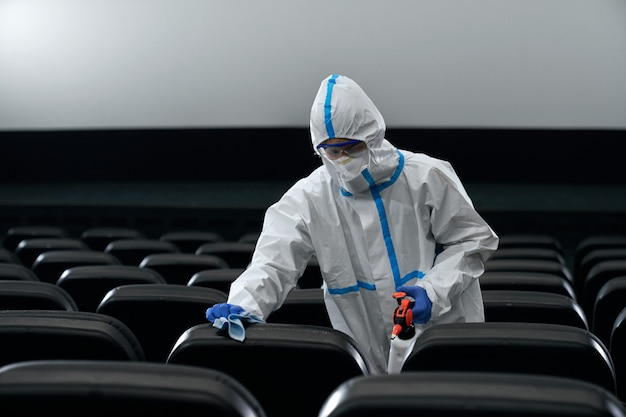 Mężczyzna w kombinezonie ochronnym dezynfekuje salę kinową