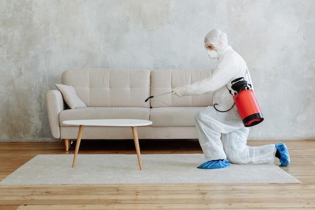 Mężczyzna w kombinezonie ochronnym dezynfekuje swoje mieszkanie. ochrona przed chorobą covid-19. zapobieganie rozprzestrzenianiu się wirusa zapalenia płuc na powierzchni. chemiczna dezynfekcja przed wirusami