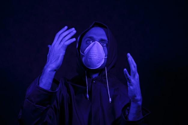 Mężczyzna w kombinezonie ochronnym i białej masce w ciemnym pokoju. koncepcja obrazu halloween. wirus ochrona. podświetlany kolorowymi światłami