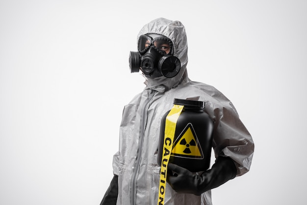 Mężczyzna w kombinezonie ochronnym i masce gazowej trzyma czarny słoik odpadów radioaktywnych i żółtą taśmę ostrzegawczą.