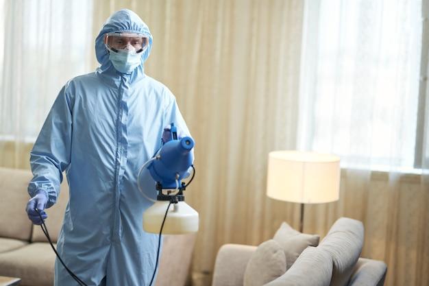 Mężczyzna w kombinezonie ochronnym i okularach za pomocą pistoletu mikrocząsteczkowego do zapobiegania wirusom w mieszkaniach. koncepcja koronawirusa i kwarantanny