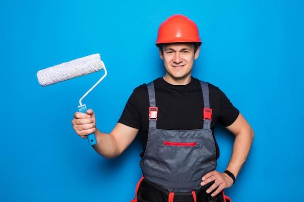 Mężczyzna w kombinezonie ochronnym kask ochronny trzymać wałek malarski instrumenty akcesoria do remontu pokoju w mieszkaniu