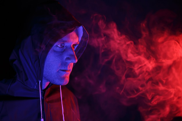 Mężczyzna w kombinezonie ochronnym wypuszcza dym. koncepcja obrazu halloween. wirus ochrona. podświetlany kolorowymi światłami