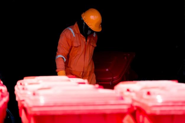 Mężczyzna w kombinezonie ochronnym z czerwonym koszem na infekcje i workiem na odpady infekcyjne.