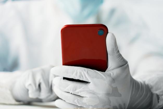 Mężczyzna w kombinezonie ochronnym z czerwonym smartfonem
