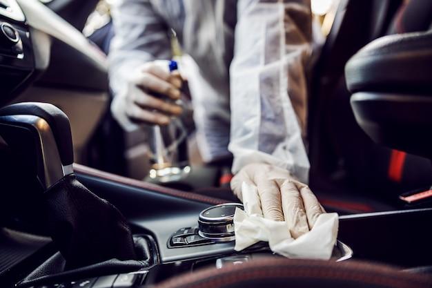 Mężczyzna w kombinezonie ochronnym z maską dezynfekującą wnętrze samochodu, wyciera czyste powierzchnie, które są często dotykane, zapobiega zakażeniu koronawirusem, zakażeniu zarazkami czy bakteriami. infekcja