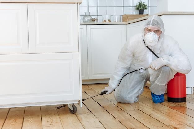 Mężczyzna w kombinezonie ochronnym ze środkiem dezynfekującym w sprayu do dezynfekcji artykułów gospodarstwa domowego i mebli. pojęcie pandemicznej dezynfekcji koronawirusa lub covid-19. dezynfekcja domu