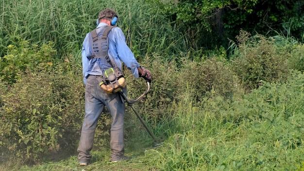 Mężczyzna w kombinezonie, okularach ochronnych, dźwiękochłonnych słuchawkach i rękawicach roboczych kosi trawę