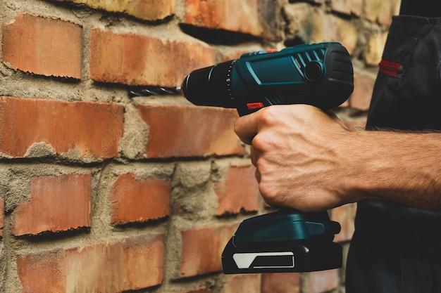 Mężczyzna w kombinezonie posiada wiertarkę akumulatorową na ścianie z cegły