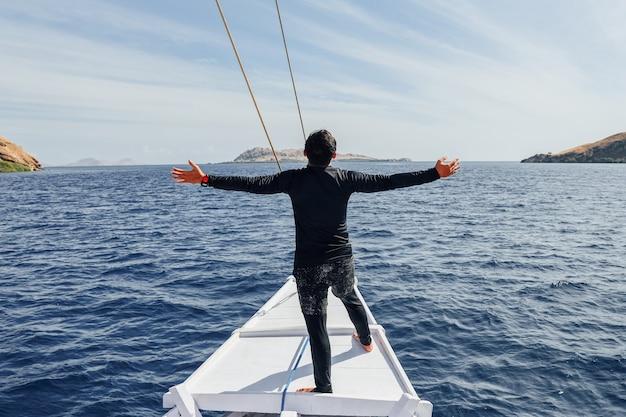 Mężczyzna w kombinezonie stojący na brzegu łodzi i cieszący się letnimi wakacjami