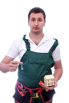 Mężczyzna w kombinezonie trzyma drewniany model domu i klucz
