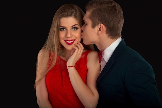 Mężczyzna w kostiumie całuje kobietę z czerwonymi ustami