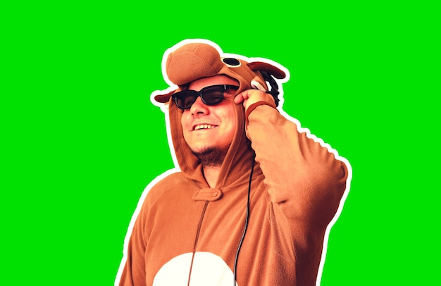Mężczyzna w kostiumie cosplay krowy na białym tle na zielonym tle. facet w piżamie dla zwierząt. śmieszne zdjęcie z pomysłami na imprezę. dyskotekowa muzyka retro.