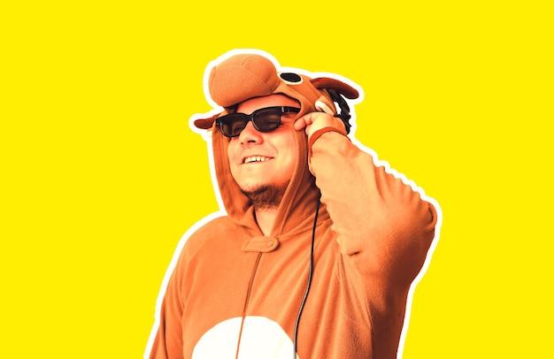 Mężczyzna w kostiumie cosplay krowy na białym tle na żółtym tle. facet w piżamie dla zwierząt. śmieszne zdjęcie z pomysłami na imprezę. dyskotekowa muzyka retro.