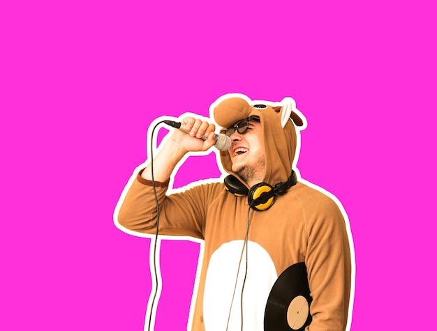Mężczyzna w kostiumie cosplay krowy śpiewającej karaoke na białym tle na fioletowym tle. facet w zabawnej piżamie zwierzęcej trzyma mikrofon. śmieszne zdjęcie. pomysły na imprezy. muzyka disco.