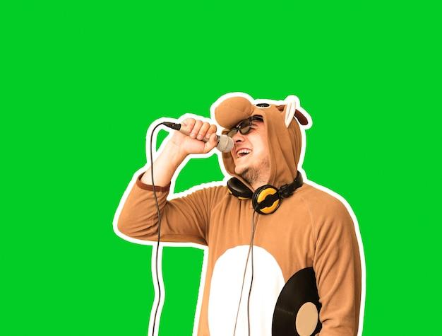 Mężczyzna w kostiumie cosplay krowy śpiewającej karaoke na białym tle na zielonym tle. facet w zabawnej piżamie zwierzęcej trzyma mikrofon. śmieszne zdjęcie. pomysły na imprezy. muzyka disco.