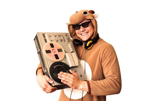 Mężczyzna w kostiumie cosplay krowy z magnetofonem szpulowym na białym tle. facet w piżamie dla zwierząt. śmieszne zdjęcie z pomysłami na imprezę. dyskotekowa muzyka retro.