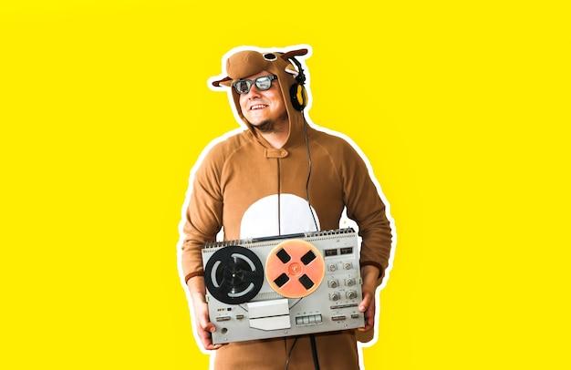 Mężczyzna w kostiumie cosplay krowy z magnetofonem szpulowym na białym tle na żółtym tle. facet w piżamie dla zwierząt. śmieszne zdjęcie z pomysłami na imprezę. dyskotekowa muzyka retro.